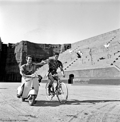 American actor Charlton Heston and British actor Stephen Boyd, wearing stage costumes, having fun in riding a Vespa and a bicycle on the set of the film 'Ben Hur' in the studios of Cinecittà. Rome, 1958